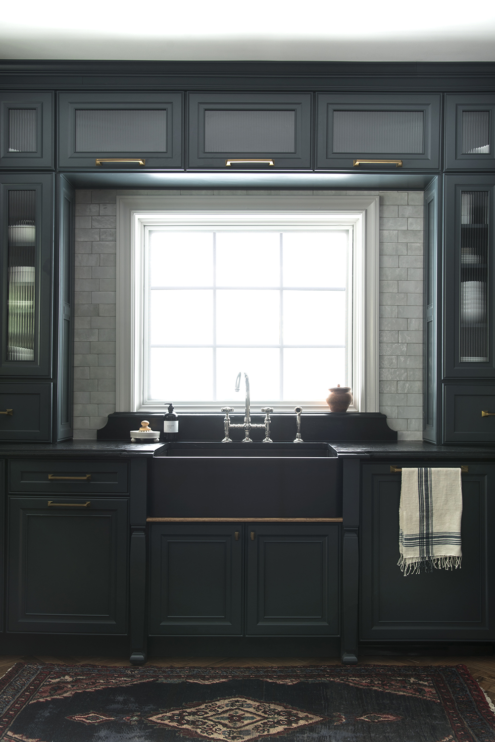 Black Kitchen Sink Surrounded by Cabinets with Vintage Rug ...